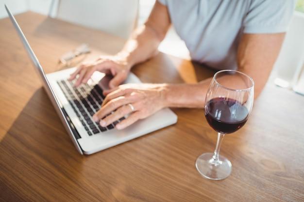 Skupiający Się Starszy Mężczyzna Używa Laptop I Pijący Wino W Domu Premium Zdjęcia