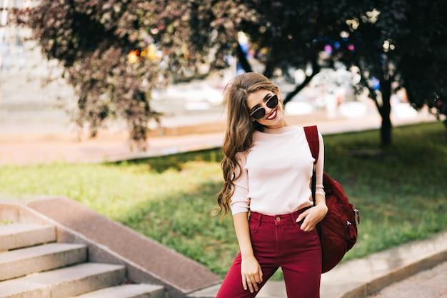 Skuteczna Dziewczyna Z Długimi Kręconymi Włosami W Winnych Spodniach Pozuje Na Ulicy W Mieście. Darmowe Zdjęcia