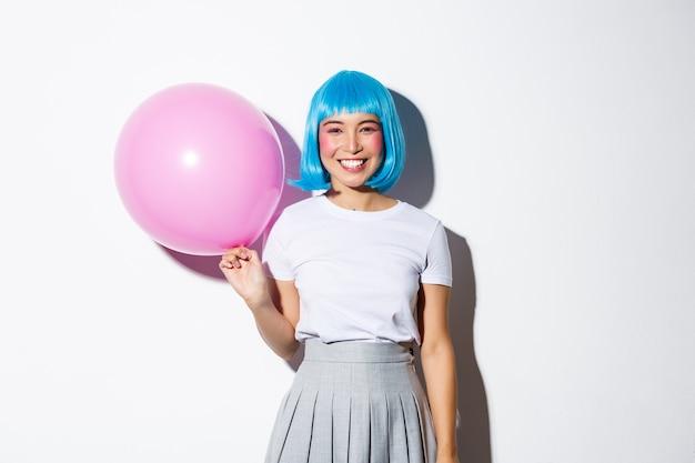 Śliczna Azjatka W Niebieskiej Peruce I Stroju Uczennicy Na Halloween, Trzymająca Różowy Balon I Uśmiechnięta, Stojąca. Darmowe Zdjęcia