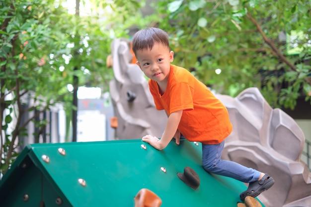 Śliczna Azjatycka Berbeć Chłopiec Ma Zabawę Próbuje Wspinać Się Na Sztucznych Głazach Przy Boiskiem Na Naturze Premium Zdjęcia