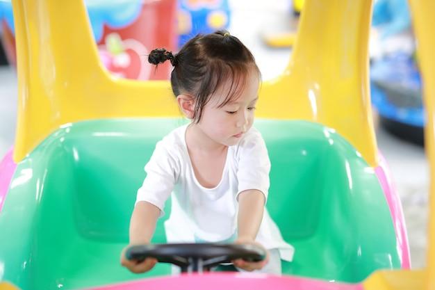 Śliczna Azjatycka Dziecko Bawić Się W Zabawkarskim Samochodzie, Bawić Się Ziemię Premium Zdjęcia