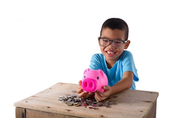 Śliczna azjatykcia chłopiec bawić się z prosiątko bankiem Premium Zdjęcia