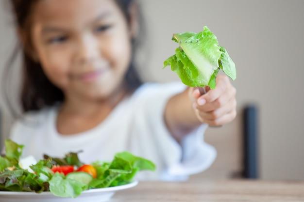 Śliczna Azjatykcia Dziecko Dziewczyna Je Zdrowych Warzywa I Mleko Dla Jej Posiłku Premium Zdjęcia