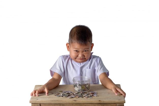 Śliczna azjatykcia kraj chłopiec zabawę z monetami w szklanym pucharze odizolowywającym na bielu Premium Zdjęcia
