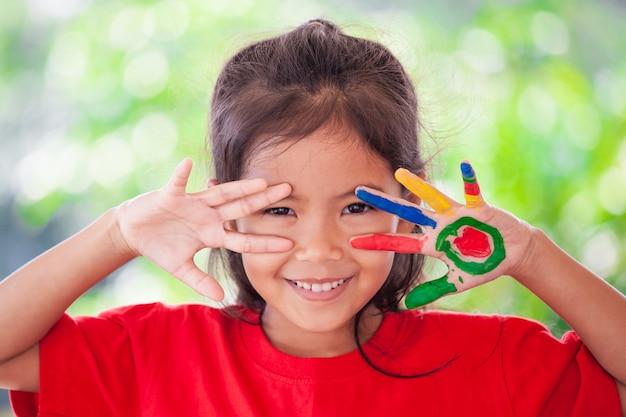 Śliczna Azjatykcia Małe Dziecko Dziewczyna Ono Uśmiecha Się Z Zabawą I Szczęściem Z Malować Rękami Premium Zdjęcia