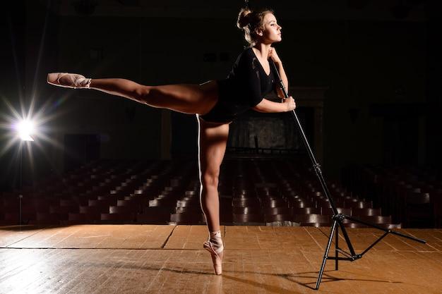 Śliczna Baletnica W Pointe Butach Robiących Klapkę Nogi Trzymającej Się Za Ręce Na Stojaku Na Scenie Premium Zdjęcia