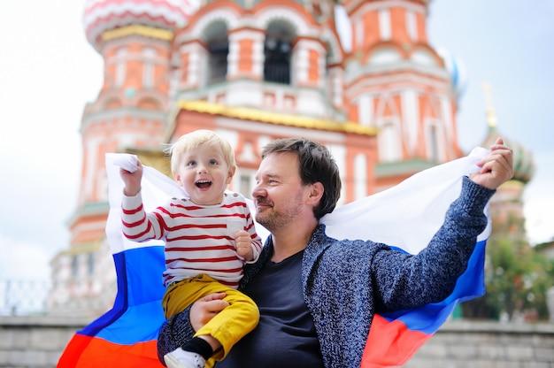Śliczna berbeć chłopiec i jego wieka średniego ojca mienia rosjanina flaga z świątobliwą basil katedrą Premium Zdjęcia