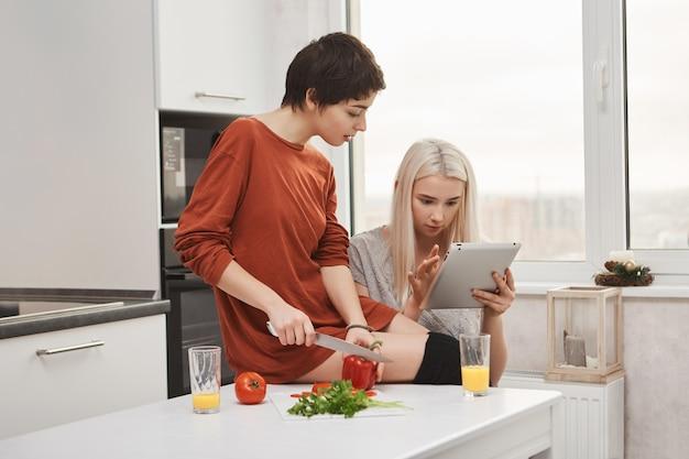 Śliczna Blondynka Czyta Ze Swoją Dziewczyną Paszę W Tablecie, Gdy Kroi Warzywa, Przygotowując Sałatkę Darmowe Zdjęcia