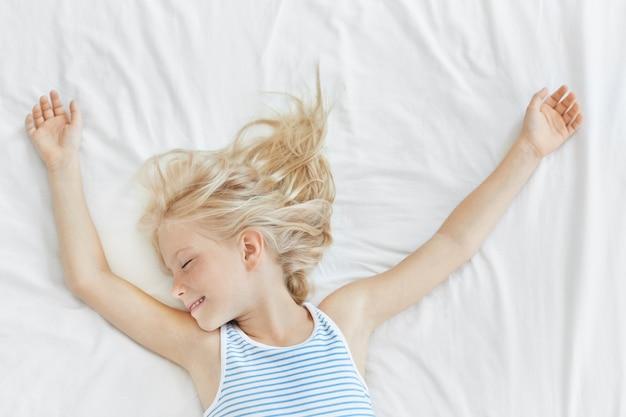 Śliczna Blondynka W Marynarskiej Koszulce śpi Na Wygodnym łóżku Na Białej Pościeli, Uśmiechnięta, Mając Przyjemne Sny. Mała Dziewczynka Czuje Się Zrelaksowana W łóżku Po Długich Grach Darmowe Zdjęcia