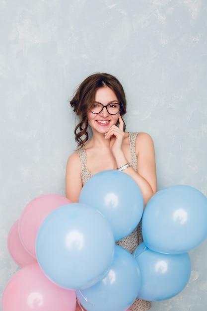 Śliczna Brunetka Dziewczyna Stojąca W Studio, Uśmiechnięta Szeroko I Trzymając Niebieskie I Różowe Balony. . Dotyka Okularów Darmowe Zdjęcia