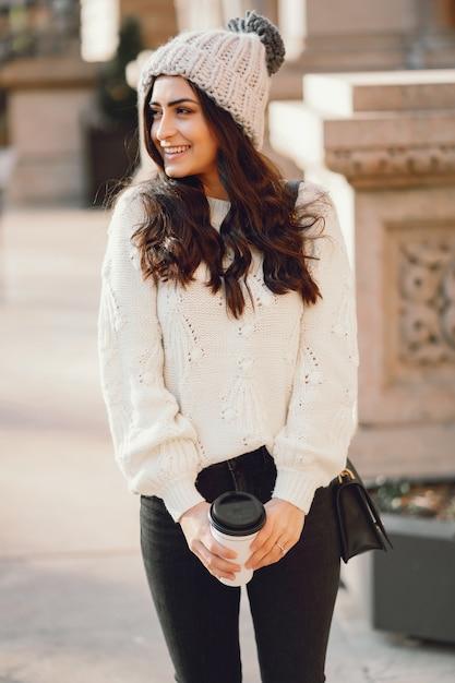 Śliczna brunetka w białym pulowerze w mieście Darmowe Zdjęcia