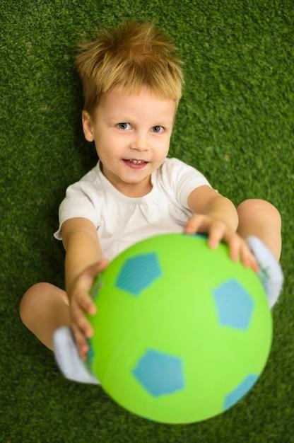 Śliczna chłopiec bawić się z futbolem Darmowe Zdjęcia