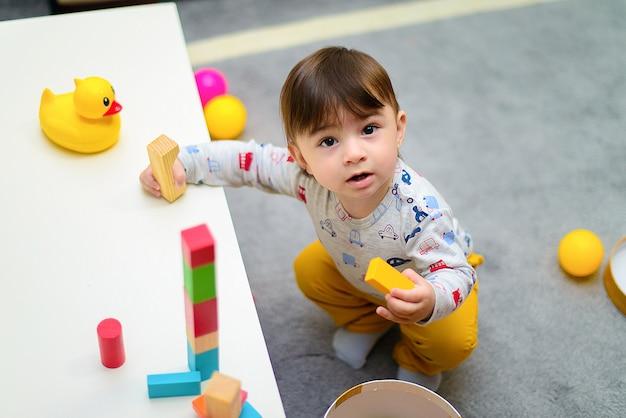 Śliczna chłopiec cieszy się podczas gdy bawić się z zabawkami lub blokami przy jego pokojem Premium Zdjęcia