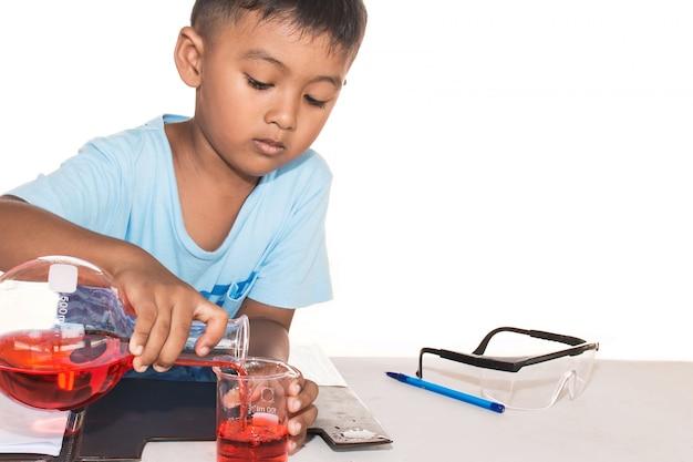 Śliczna chłopiec robi nauka eksperymentowi, nauki edukacja, azjata dzieciaki i nauka eksperymenty na białym tle Premium Zdjęcia