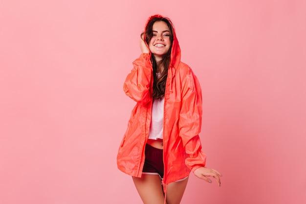 Śliczna Ciemnowłosa Kobieta W Białej Koszulce I Pomarańczowej Wiatrówce śmieje Się Na Różowej ścianie Darmowe Zdjęcia