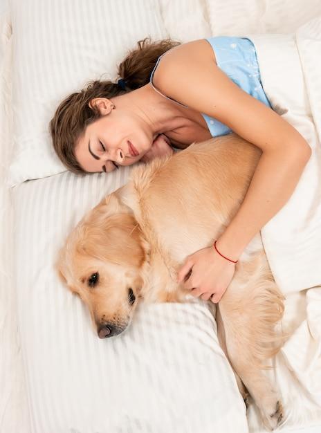 Śliczna Dziewczyna Obejmuje Jej Psiego Aporteru W Sypialni Indoors Premium Zdjęcia