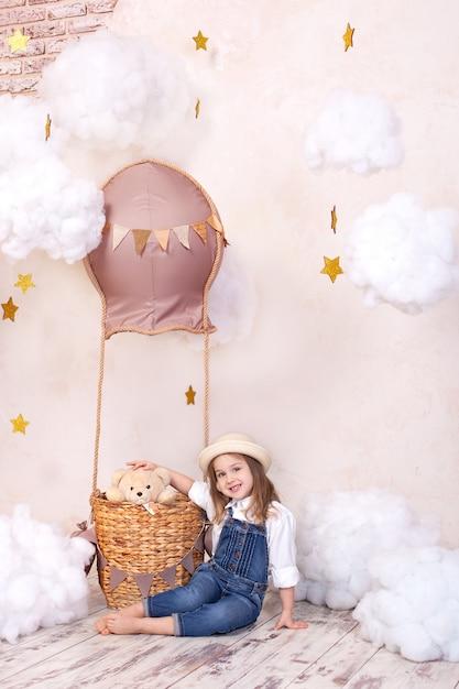 Śliczna Dziewczyna Siedzi Na ścianie Balon, Gwiazdy I Chmury I Trzyma Misia. Mała Dziewczynka Marzy. Dziewczynka Bawi Się Zabawką W Pokoju Dziecięcym. Wystrój Pokoju Dziecięcego. Zabawki Dla Niemowląt I Pluszowe Premium Zdjęcia