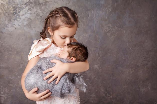 Śliczna dziewczyna trzyma jej młodszego brata. szczęśliwa siostra całuje swojego nowonarodzonego brata. copyspace Premium Zdjęcia