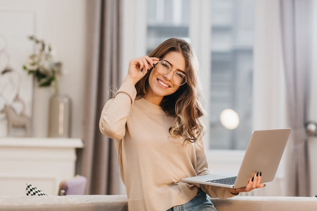 Śliczna Dziewczyna W Beżowej Koszuli Dotykając Okularów I Trzymając Laptop Z Uśmiechem Darmowe Zdjęcia