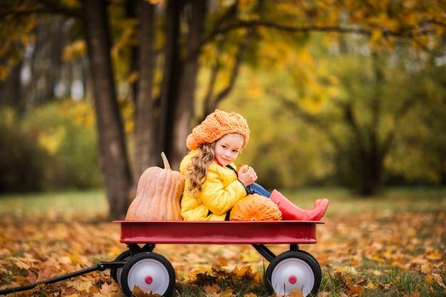 Śliczna Dziewczyna W żółtym Płaszczu Przeciwdeszczowym, Czerwone Gumowe Buty W Parku Jesień Premium Zdjęcia