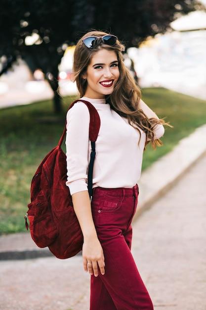 Śliczna Dziewczyna Z Długimi Włosami Uśmiecha Się W Parku Miejskim. Ma Na Sobie Kolor Marsala. Wygląda Na Zadowoloną. Darmowe Zdjęcia