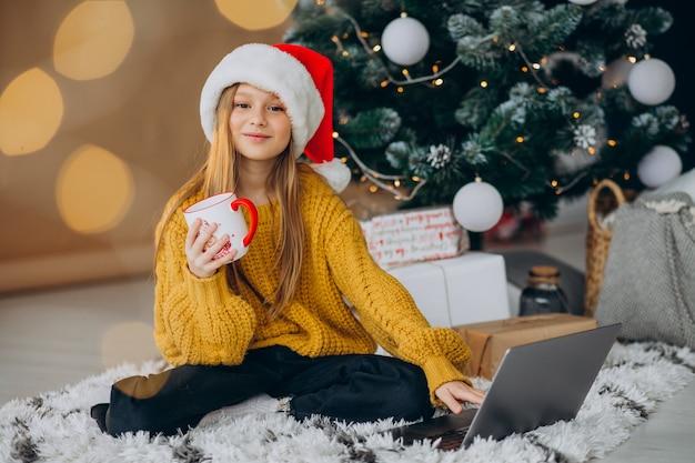 Śliczna Dziewczyna Za Pomocą Komputera Przy Choince Darmowe Zdjęcia