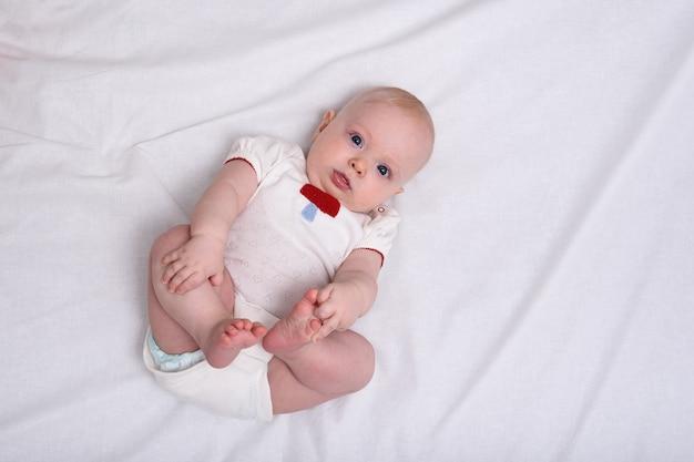 Śliczna Dziewczynka Noworodka W Pieluchach Na Białych Prześcieradłach. Widok Z Góry Premium Zdjęcia