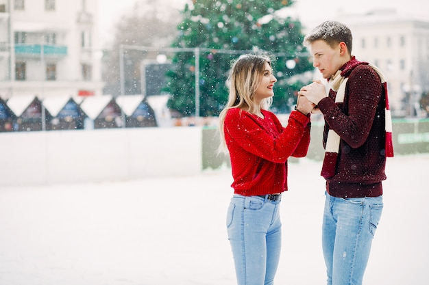 Śliczna i kochająca para w czerwonych swetrach w zimowym mieście Darmowe Zdjęcia
