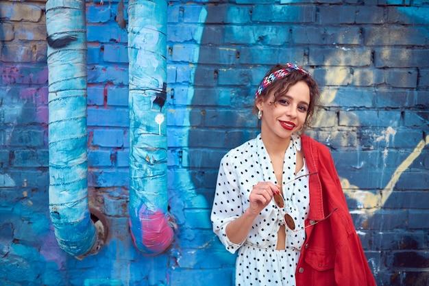 Śliczna I Piękna Dziewczyna W Białej Sukni I Czerwonej Kurtce Na Tle Niebieski Mur Z Cegły Premium Zdjęcia