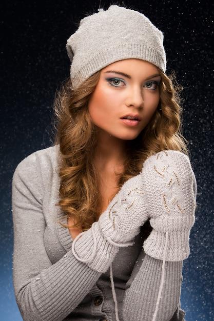 Śliczna kędzierzawa dziewczyna jest ubranym mitynki podczas śniegu Darmowe Zdjęcia