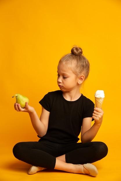 Śliczna Mała Blondynki Dziewczyna Wybiera Między Bonkretą I Słodkimi Lody Na żółtym Tle Premium Zdjęcia