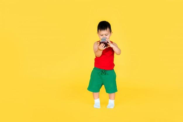 Śliczna Mała Chłopiec W Czerwonej Koszulce I Zieleni Krótkim Z Filiżanką Sok Na Kolorze żółtym Premium Zdjęcia