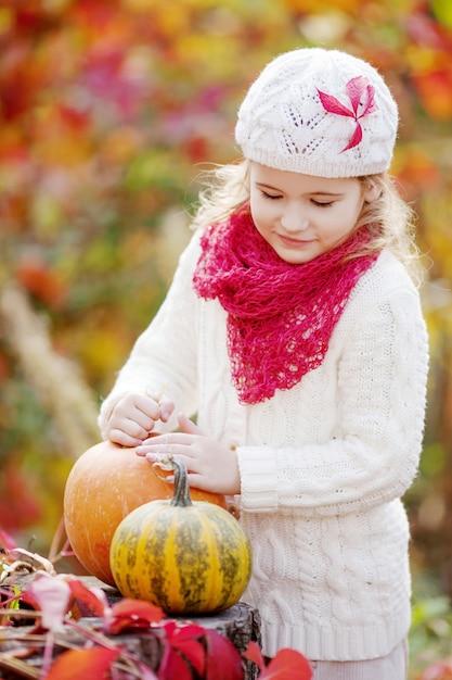 Śliczna mała dziewczynka bawić się z baniami w jesień parku. jesienne zajęcia dla dzieci Premium Zdjęcia