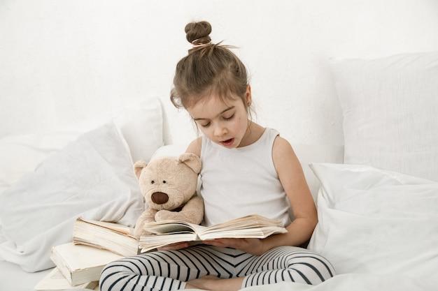 Śliczna Mała Dziewczynka Czytając Książkę Na łóżku W Sypialni. Darmowe Zdjęcia