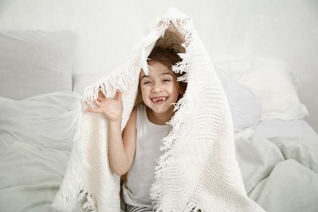 Śliczna Mała Dziewczynka Gra W łóżku Z Kocem Po Spaniu Darmowe Zdjęcia