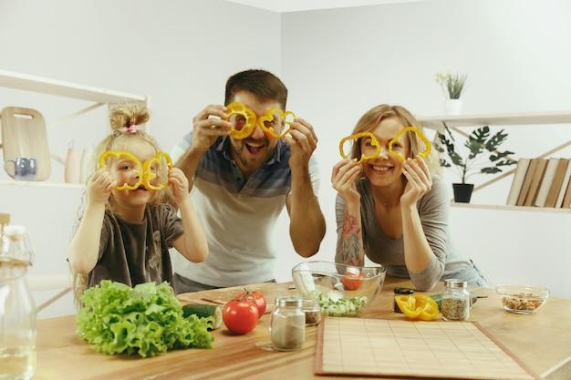 Śliczna Mała Dziewczynka I Jej Piękni Rodzice Kroją Warzywa I Uśmiechają Się, Robiąc Sałatkę W Kuchni W Domu Darmowe Zdjęcia