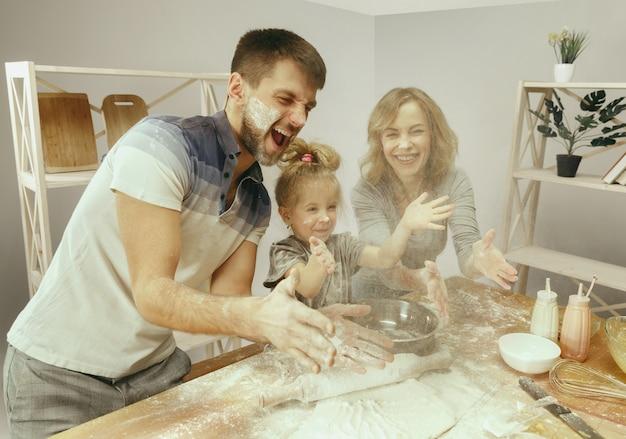 Śliczna Mała Dziewczynka I Jej Piękni Rodzice Przygotowują Ciasto Na Ciasto W Kuchni W Domu. Darmowe Zdjęcia