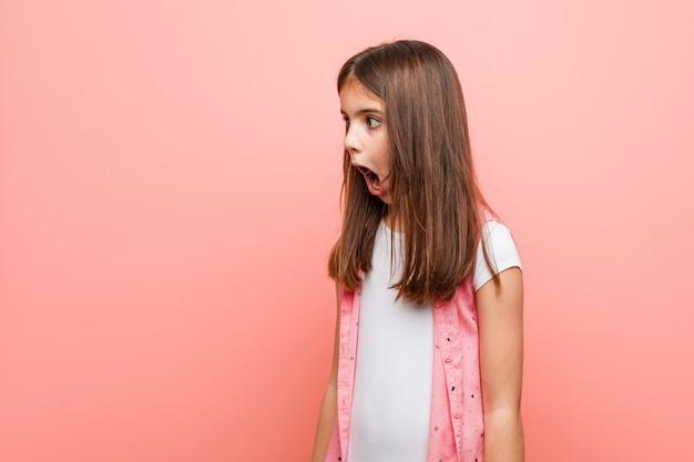 Śliczna mała dziewczynka jest zszokowana z powodu czegoś, co widziała. Premium Zdjęcia