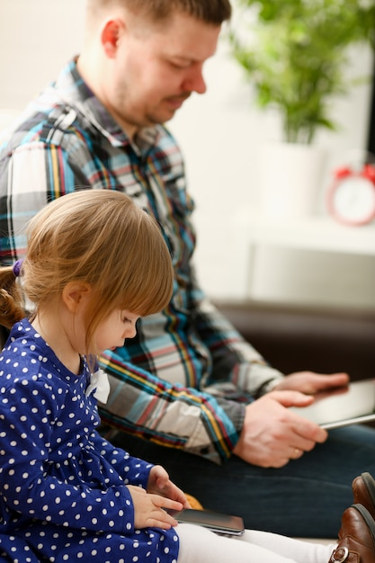 Śliczna Mała Dziewczynka Na Leżance Z Tata Use Telefonem Komórkowym Premium Zdjęcia