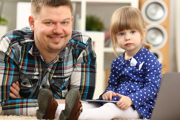 Śliczna Mała Dziewczynka Na Podłogowym Dywanie Z Tata Premium Zdjęcia