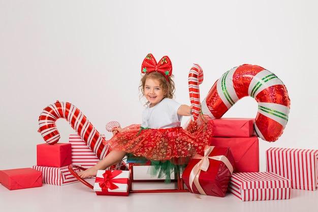 Śliczna Mała Dziewczynka Otoczona świątecznymi Elementami Premium Zdjęcia