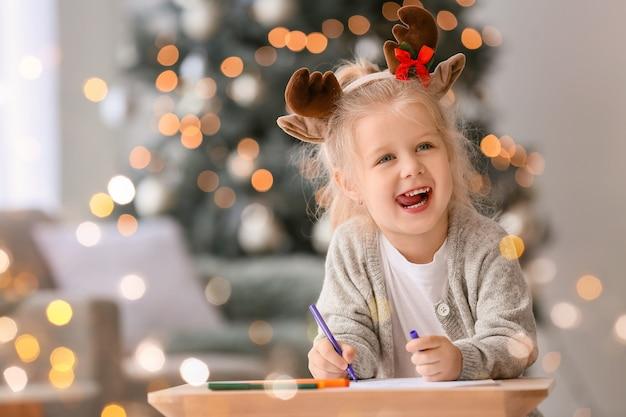 Śliczna Mała Dziewczynka Pisze List Do świętego Mikołaja W Domu Premium Zdjęcia