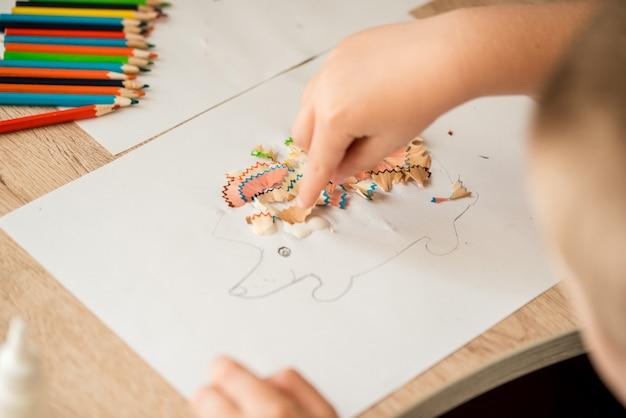 Śliczna Mała Dziewczynka Robi Aplikacji Klei Kolorowemu Domowi, Nakładając Kolorowy Papier Za Pomocą Kleju, Wykonując Dzieła Sztuki I Rzemiosła W Przedszkolu Lub W Domu. Pomysł Na Kreatywność Dzieci, Projekt Artystyczny Wykonany Z Papieru. Premium Zdjęcia