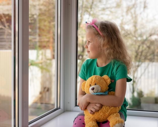 Śliczna Mała Dziewczynka Siedzi Z Jej Misiem Blisko Okno I Patrzeje Na Zewnątrz. Zamyślone Dziecko Premium Zdjęcia