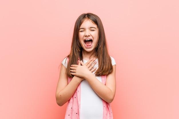 Śliczna mała dziewczynka śmia się utrzymujący ręki na sercu, szczęście. Premium Zdjęcia