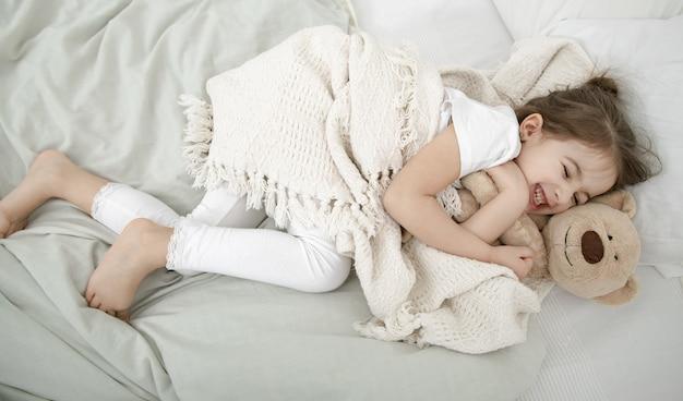 Śliczna Mała Dziewczynka śpi W łóżku Z Zabawką Pluszowego Misia. Darmowe Zdjęcia