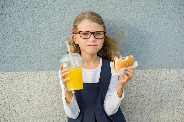 Śliczna mała dziewczynka trzyma hamburgeru sok pomarańczowego Premium Zdjęcia