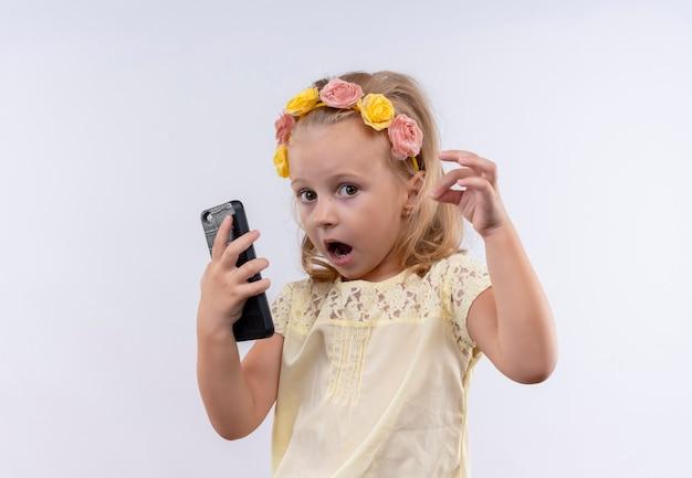 Śliczna Mała Dziewczynka Ubrana W żółtą Koszulkę W Kwiecistej Opasce Zaskakująca, Trzymając Telefon Komórkowy Na Białej ścianie Darmowe Zdjęcia