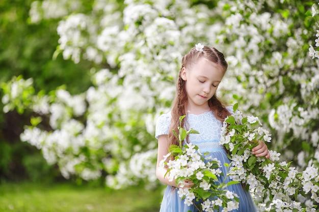 Śliczna mała dziewczynka w kwitnącym jabłoń ogródzie przy wiosną Premium Zdjęcia