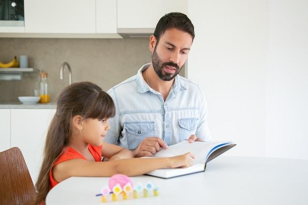 Śliczna Mała Dziewczynka, Wskazując Na Tekst I Ucząc Się Z Tatą. Darmowe Zdjęcia